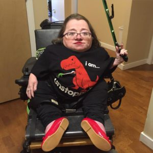 Priscilla in black pants, and red slip-on shoes is holding a green reacher tool in left hand and wearing a black t-shirt that says