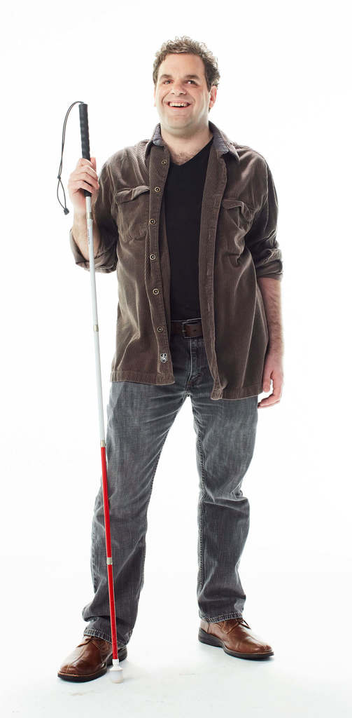 Photo of Dave with his cane and his typical big grin.
