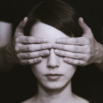 A person covering a womans eyes