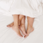 Man and Woman in bed with feet hanging out of white bed sheets