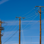 Three Telephone Poles in a row with a blue sky background