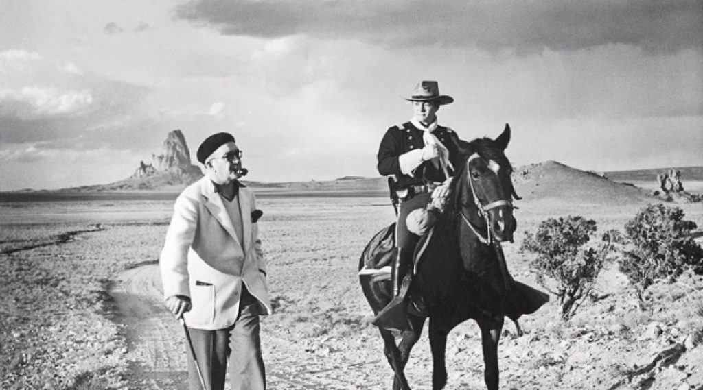 Black and White Photo: John Wayne Riding a horse wearing a cowboy hat and John Ford Standing next to him wearing a beret, white coat and using a cane in the desert with a few trees in the background