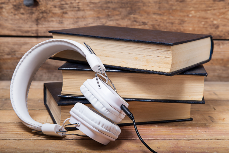 Stack of 3 books with black covers with a white pair of headphones next to them on a wood table